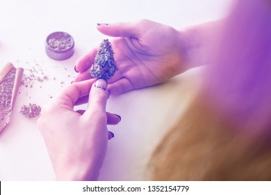 Close up of marijuana blunt with grinder. marijuana use concept. Woman rolling a cannabis blunt on white background. Woman preparing and rolling marijuana cannabis joint. Color toning