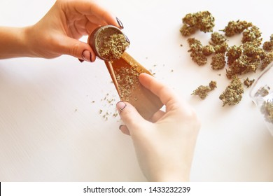 Close up of marijuana blunt with grinder. Woman preparing and rolling marijuana cannabis joint. Marijuana use concept. Woman rolling a marijuana joint on white background.