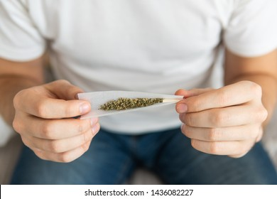 Close up of marijuana joint with grinder. marijuana use concept. Man preparing and rolling marijuana cannabis joint. Man rolling a cannabis joint on white background.