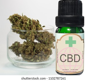 close up of marijuana plant in a glass container and cbd oil