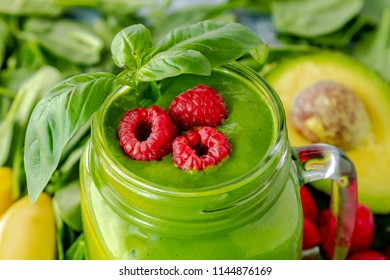 Close up of mason jar mug filled with spinach and kale green smoothie with ingredients garnished with raspberries and basil leaves