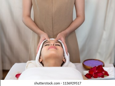 close up of masseur hand which rejuvenating and doing massage on female head and people, beauty, spa, healthy lifestyle and relaxation concept  at Spa salon