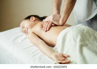 close up masseur hands doing massage to the little girl