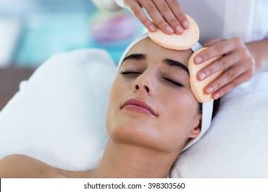 Close up of masseuse cleaning woman face with cotton swabs at spa