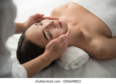 Close up of masseuse hands massaging female face. Woman closed eyes with pleasure