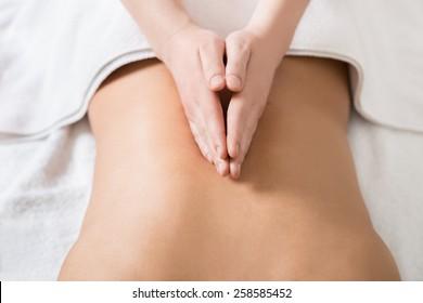 Close up of a masseuse's hands massaging female back.