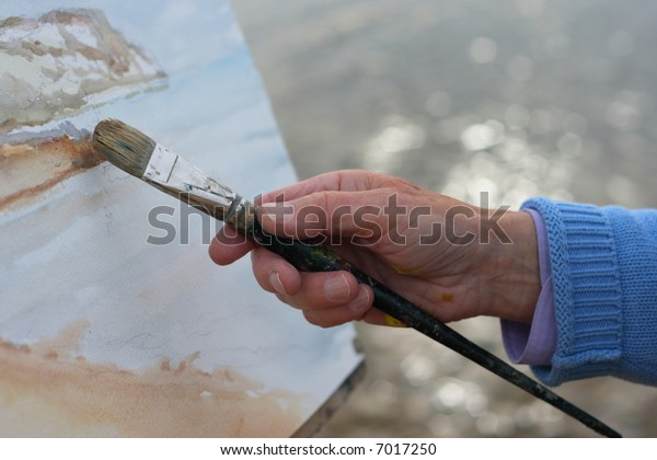A close up of a mature artists hand painting a coastal landscape.