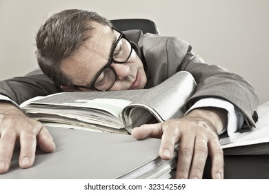 Close up of mature businessman lying on office file