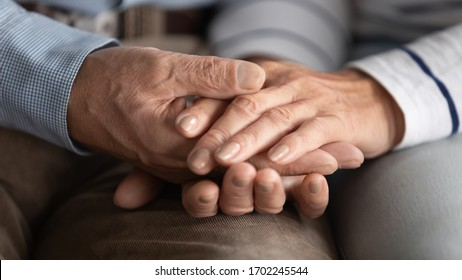Close up mature couple holding hands, loving caring wife supporting comforting senior aged husband, family expressing empathy and understanding, trusted relationship in marriage