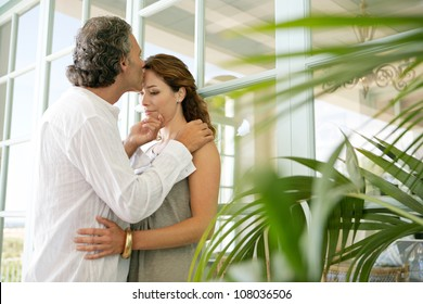Close up of a  mature couple kissing at home, standing by large glass doors.