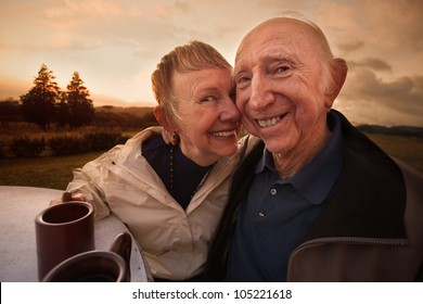 Close mature couple outside with coffee mugs