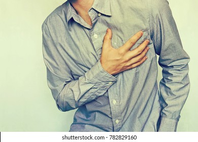 Close up mature male painful chest. Chronic heart failure. Young man with chest pain. Businessman in blue shirt with heart disease. Heart Attack. Hypertension, Hypertension, Dystonia, Stroke, Ischemia