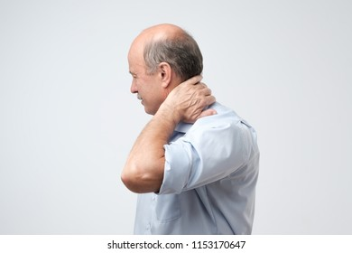 Close up of mature man in blue shirt with closed eyes touching his neck in pain. Health problems at old age, neuralgia concept