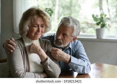 Close up mature man comforting frustrated crying woman, hugging shoulders, caring elderly husband and wife overcoming troubles, health problems, consoling and supporting, psychological help