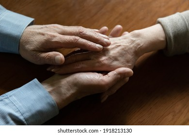 Close up mature man comforting woman, holding hands, elderly wife and husband overcoming problems together, senior family expressing empathy and understanding, trusted relationship in marriage