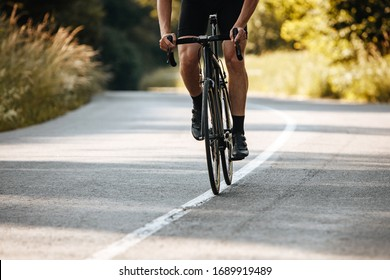 Close up of mature man with strong body shape in cycling outfit doing sport activity on bike. Concept of healthy lifestyle and regular training.