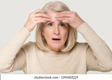 Close up mature woman touches forehead looks at aging skin feels upset about facial wrinkles portrait isolated on grey background, cosmetology botox injection procedure anti-aging treatment concept