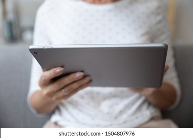 Close up mature woman using computer tablet, elderly female holding electronic device in hands, browsing apps, surfing internet, chatting or shopping online, searching information in internet