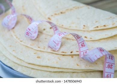 Close up of measuring tape on low carb tortillas or naan bread. Keto friendly low-carb food - a healthier option - up close image. Plain tortillas on their own.