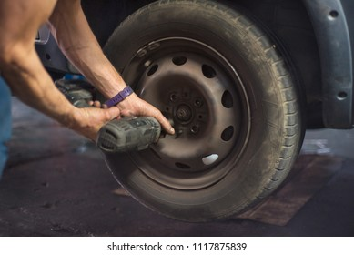 Close up of mechanic changing wheel with electric wrench.