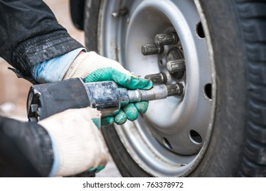 Close up of mechanic changing wheel on car with pneumatic wrench. Repair car