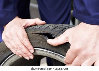 Close Up Of Mechanic Examining Damaged Car Tyre