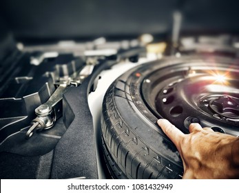 Close up mechanic hand taking spare tire at boot with light reflection in dark tone