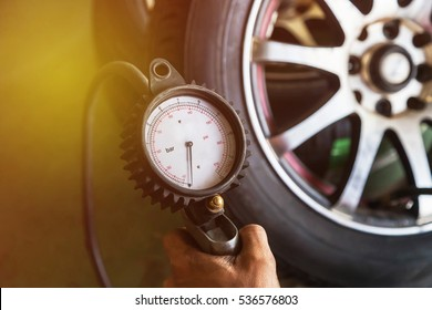 Close up mechanic inflating tire and checking air pressure with gauge