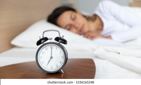 Close up mechanical alarm clock standing on bedside wooden table, showing 7 o'clock time, with blurred peaceful millennial mixed race young girl enjoying sweet dreams, resting at home on background.