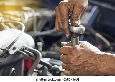 Close up mechanical man dirty hands using tool to fix repair car engine, maintenance vehicle service. dirty man hands holding tools maintenance car concept.