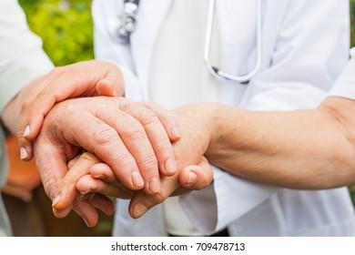 Close up medical doctor holding elderly patients shaking hands, Parkinson disease