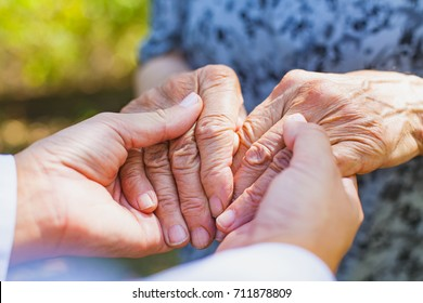 Close up medical doctor holding senior woman's shaking hands, Parkinson disease
