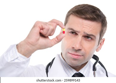 Close up of medical doctor looking small yellow-red pill  Isolated on a white background