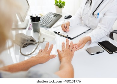 Close up of a medical examination.Middle aged woman with arthritis showing her hands to a female doctor.