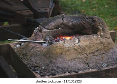 Close up of medieval blacksmith forge with furnace, burning coals, fire, tools and bellows