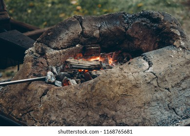 Close up of medieval furnace with burning coals, fire and tools in blacksmith forge