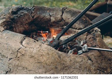 Close up of medieval furnace with iron tongs, burning coals and fire in blacksmith forge