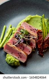 Close up of medium-rare tuna steak with broccoli puree and asparagus, served on minimalist black table