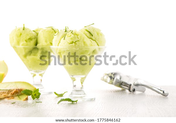 Close up of melon flavored ice-cream with mint and melon on a white table.