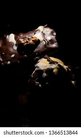 Close up of a melting chocolate brownie with dark sauce, vanilla ice-cream, a walnut and white cream.  Lit from the side the rest in  deep shadow, abstract view, tempting and decadent on black