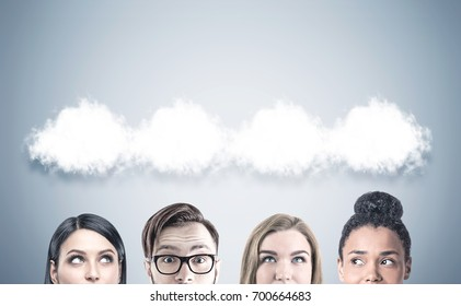 Close up of members of a business team s heads. They are standing near a gray wall with thought clouds above them. Mock up