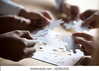 Close up members of multiracial team assembling white puzzle, African American and Caucasian people searching solution together, team building activity, staff training, support and unity