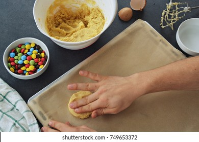 Close up - men is baking cookies with with colorful chocolate candies on a baking paper on the baking tray