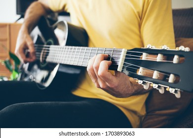 Close up of men in casual clothes is playing black color acoustic guitar at beautiful home interior. Teachers is giving guitar lessons. Natural light lifestyle photo.