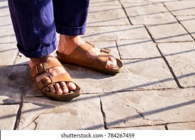 Close up of men food wearing genuine Sandal leather shoes or vintage leather sandal shoe on the concrete road