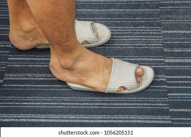 close up men wear too tight sandal on his feet in the house