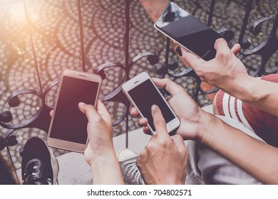 Close up of men and  woman hands holding touching mobile phone with blank copy space for your text message in cafe  with light Sunset,Vintage tone.Selective focus