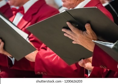 Close up of mens choir members holding singing book while performing in a cathedral in Rochester, Kent, UK