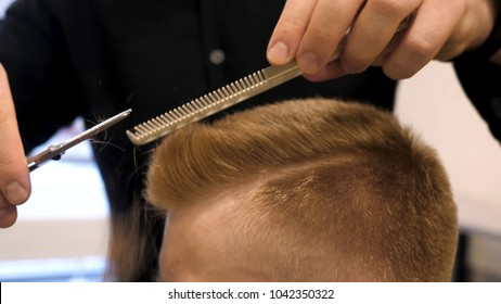 Close up of men's hair cutting scissors in a beauty salon. Master cuts hair and beard of men in the barbershop, hairdresser makes hairstyle for a young man. Close up of Man at the Hair salon
