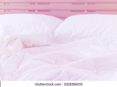 Close up messy white sheet and pillows on wood bed in bedroom interior